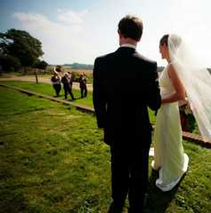 Bride and groom watch arrival of jazz band at wedding